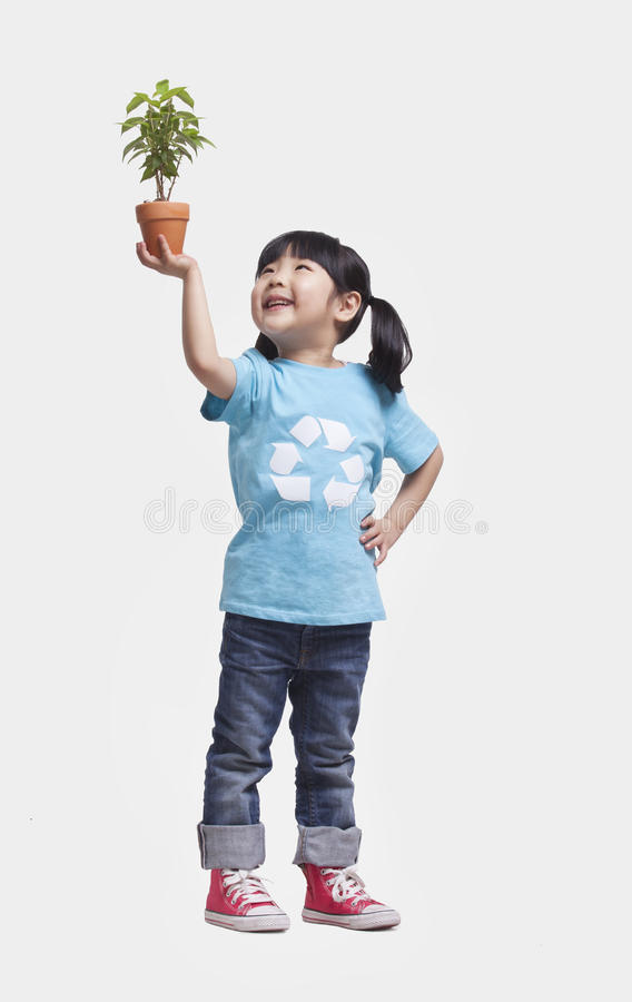 Little girl with pigtails in recycling symbol t-shirt holding potted plant above her head, studio shot stock images