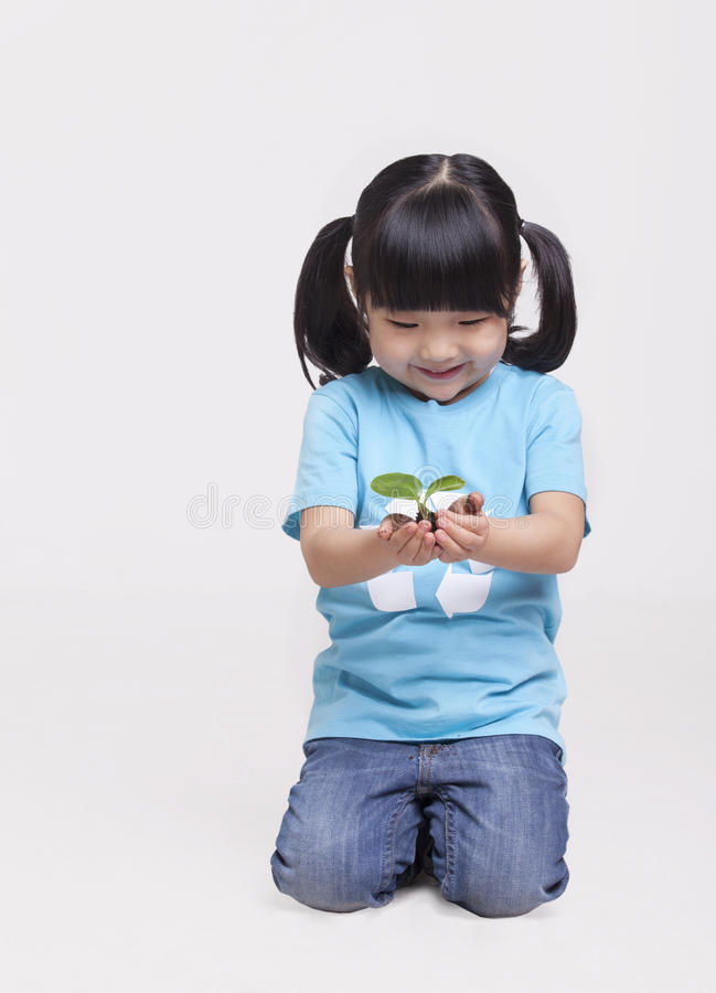 Little girl with pigtails in recycling symbol t-shirt holding a seedling, studio shot royalty free stock photos