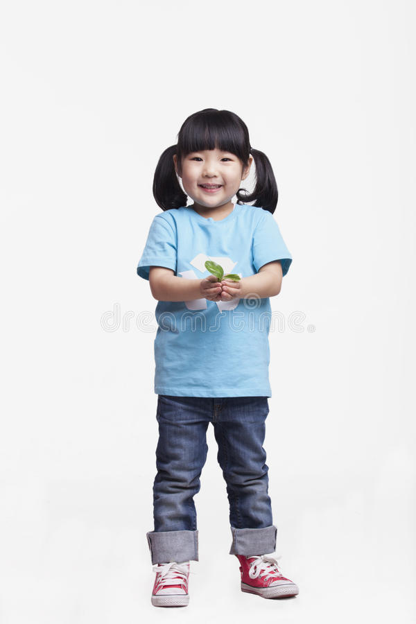 Little girl with pigtails in recycling symbol t-shirt standing and holding a seedling, studio shot stock photo