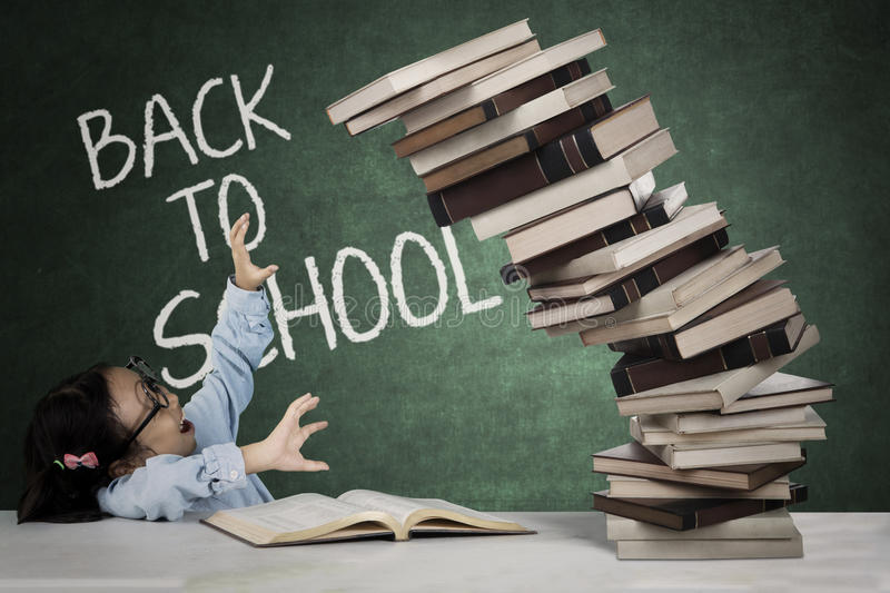 Little girl with a pile of books royalty free stock photos