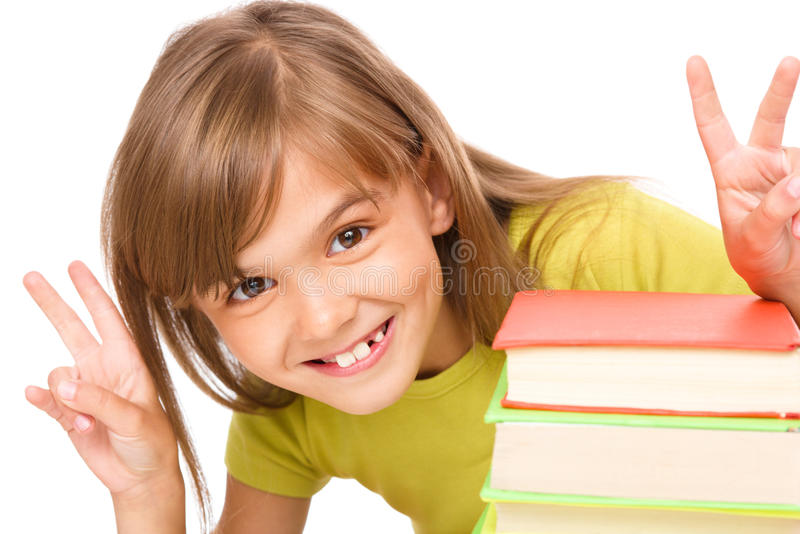 Little girl with a pile of books. And showing victory sign, isolated over white royalty free stock photos