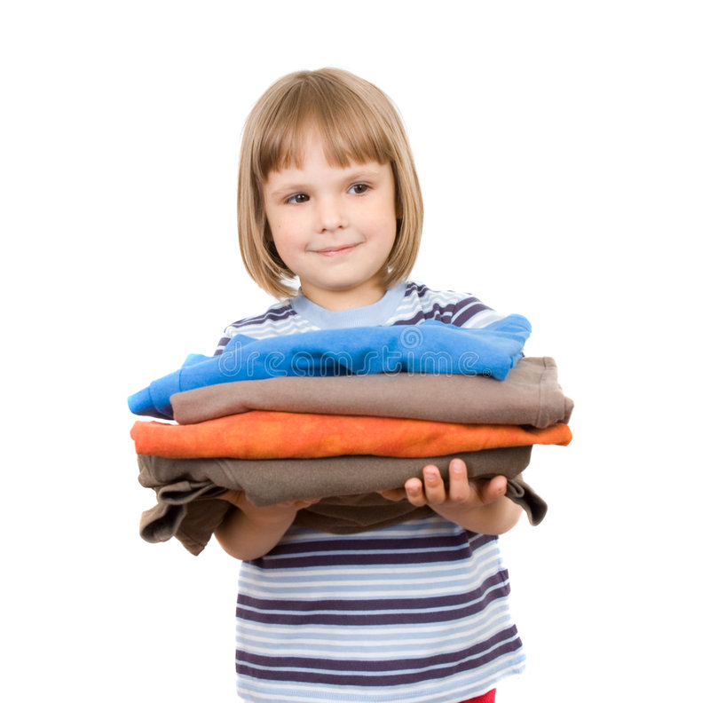 Little girl with a pile of T-shirts royalty free stock image