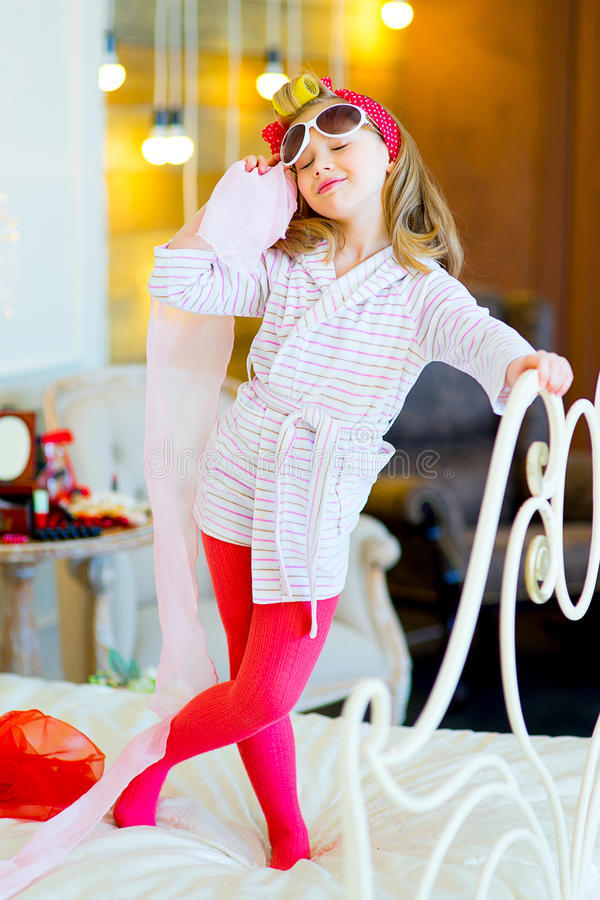The little girl in pin up style. The little girl poses in pin up style in a striped terry dressing gown, in hair curlers and with a red bandage in peas standing stock photo