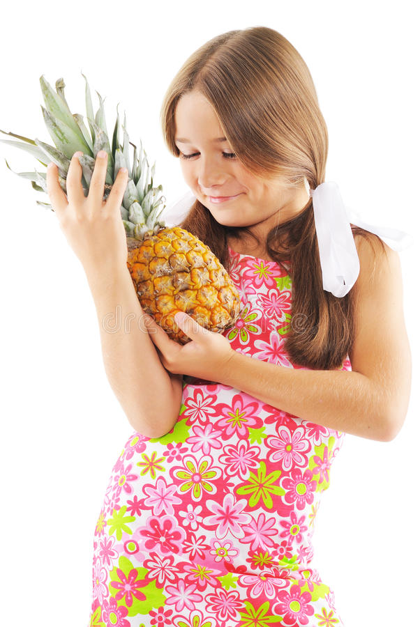 Little girl with pineapple. In hands. On white background royalty free stock photos