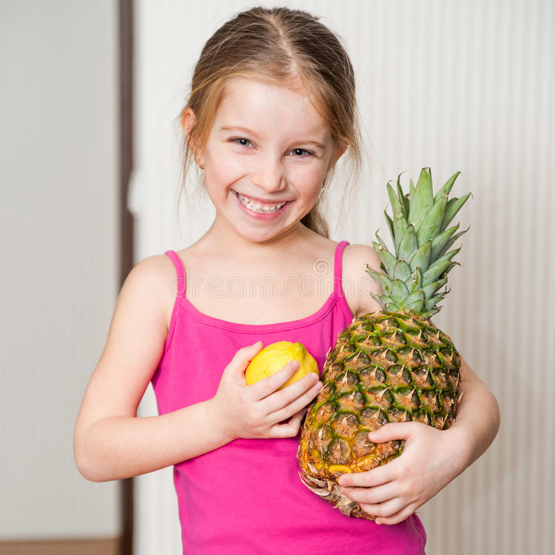 Little girl with a pineapple and lemon stock photo