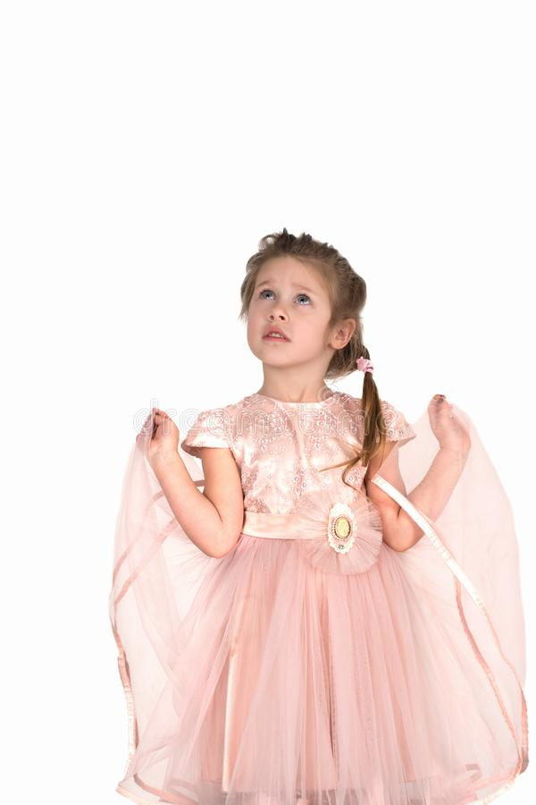 The girl in a pink airy dress looks upward. The little girl in a pink airy dress looks upward royalty free stock images