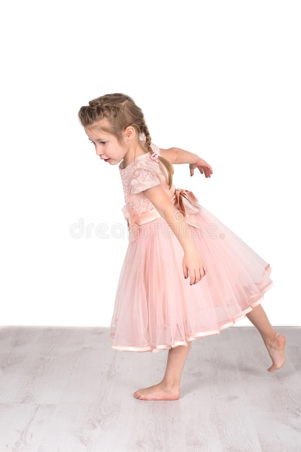 The little girl in a pink ball dress barefoot does exercise. The little girl in a pink ball dress barefoot represents that she is a ballerina. She does exercise stock photos