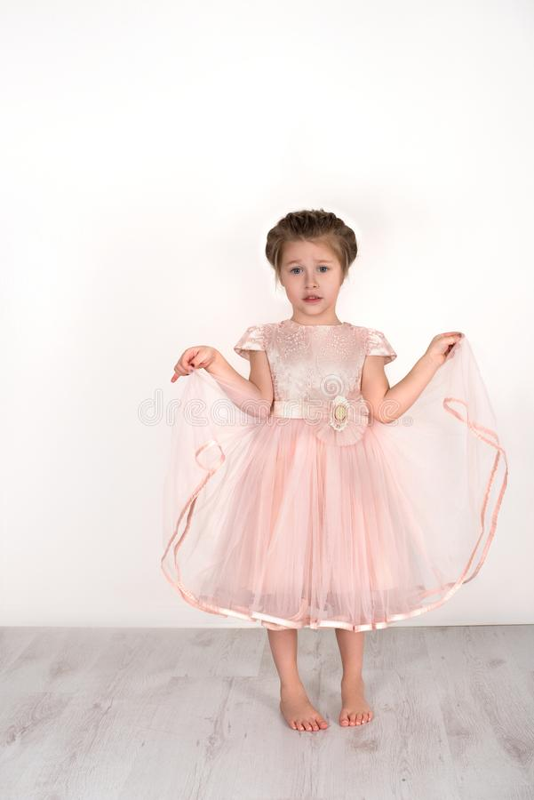 The little girl in a pink ball dress barefoot is capricious. The little girl in a pink ball dress is capricious. She upset stands barefoot on a floor in studio royalty free stock images