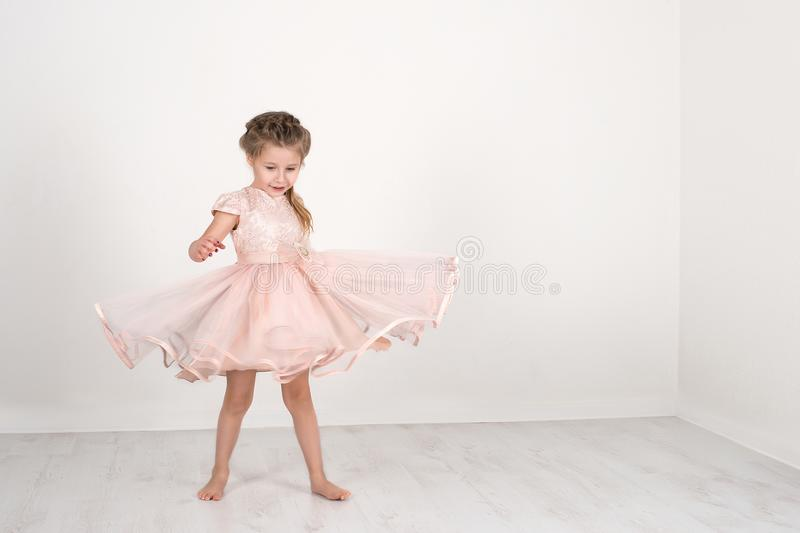 The girl in a pink ball dress to be turned in dance. The little girl in a pink ball dress to be turned in dance royalty free stock photos