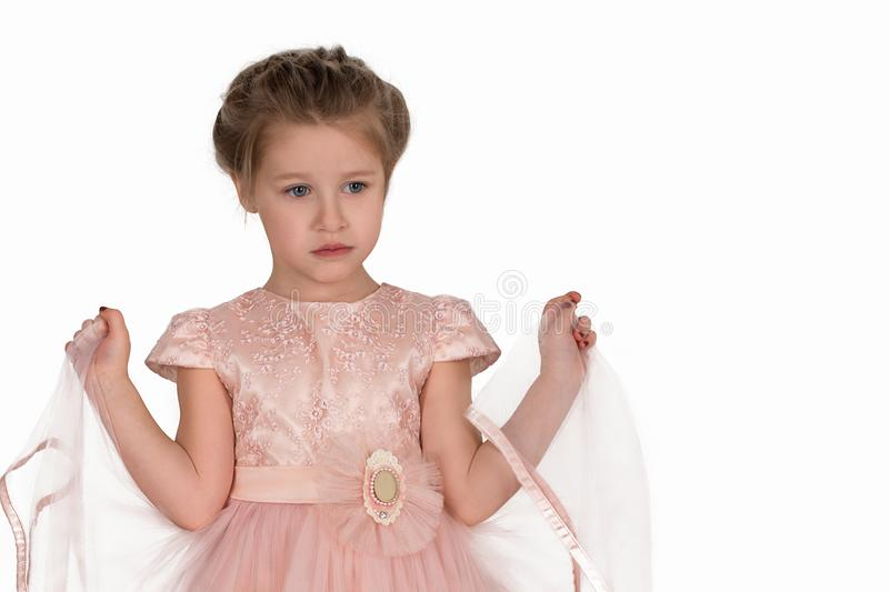The little girl in a pink ball dress on white background in stu. The little girl in a pink ball dress stands on white background in studio. She holds skirt tips royalty free stock photo