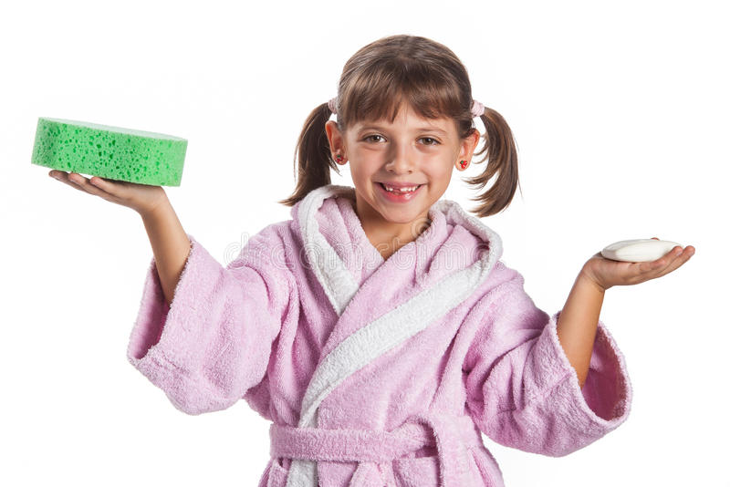 Little girl in pink bathrobe. With a sponge and a soap bar stock image