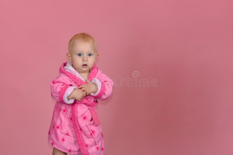 Little girl in a pink bathrobe on a pink background in the studio.  stock photography