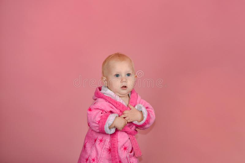 Little girl in a pink bathrobe on a pink background in the studio.  royalty free stock photography