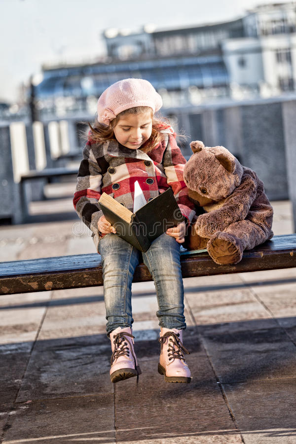 Little girl in a pink beret sits on a bench and reads the book stock photography