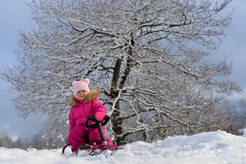 A little girl in a pink down jacket sitting on a sled under a tree in the snowy winter. stock photos
