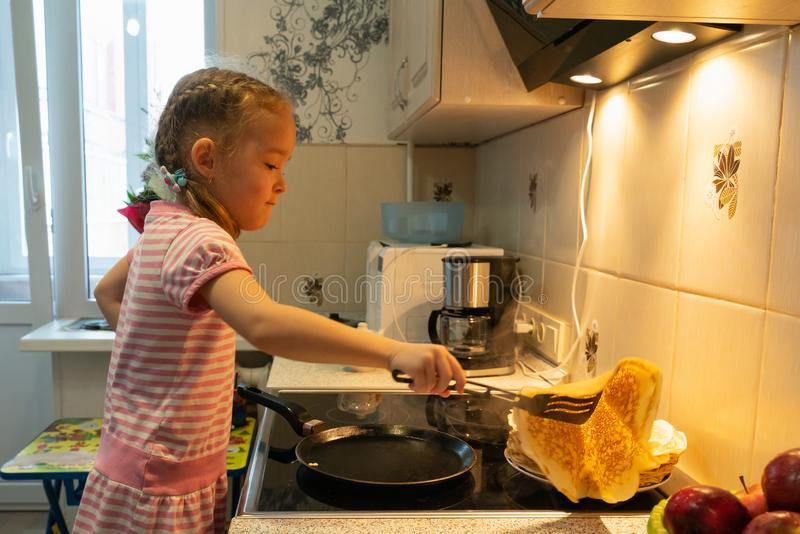A little girl in a pink dress is frying pancakes on an electric stove royalty free stock photo