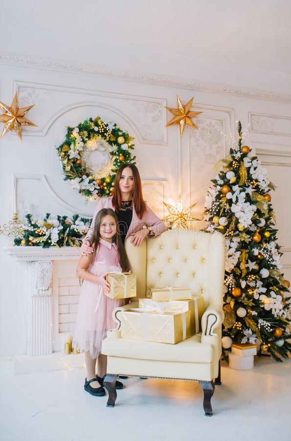 Little girl in pink dress with her mother standing near the armchair by the Christmas tree in the New Year`s room stock images