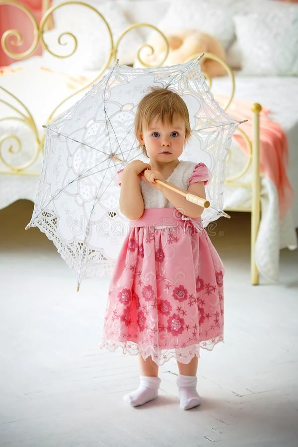 Little girl holding an umbrella for the sun stock images