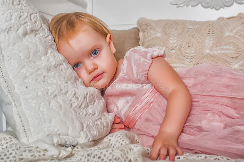 Little girl in a pink dress. Little girl in pink dress lying on the couch stock image