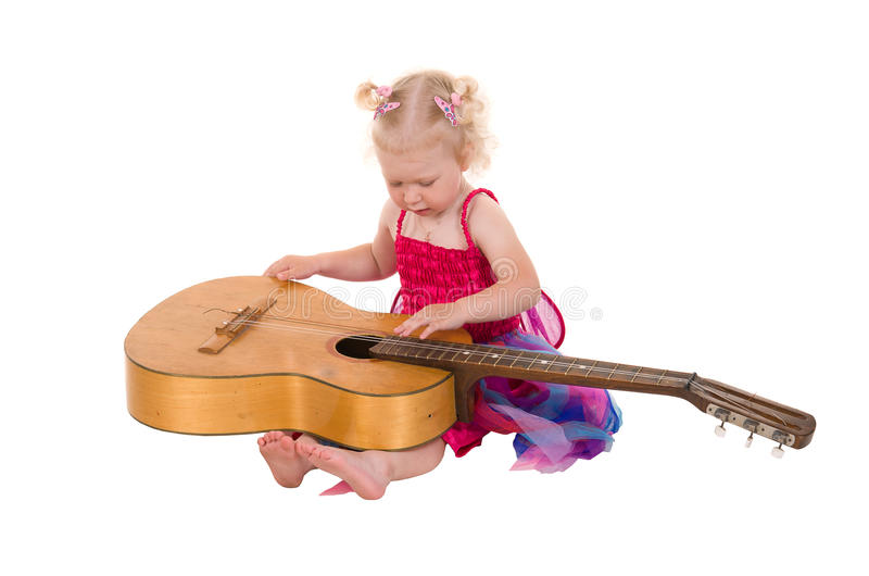 Little girl in a pink dress playing guitar stock photography