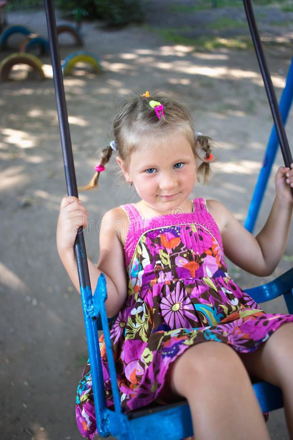 Little girl in a pink dress is riding a swing stock photos