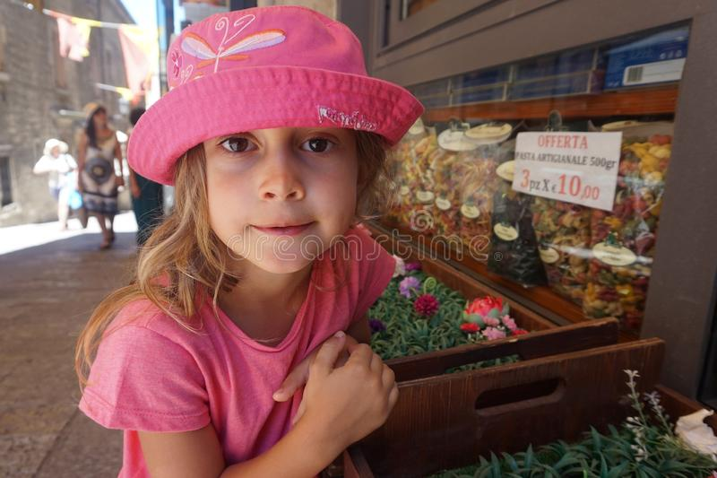 Little girl with pink hat in front of a grocery store, San Marino royalty free stock photo