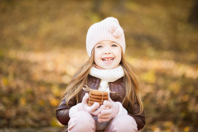 Little girl in a pink hat and leather jacket in the fall with pumpkins and leaves close up. Little girl in pink hat and leather jacket in the autumn with cookies stock images