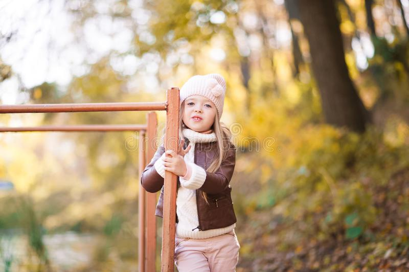 Funny portrait of a little girl. Little girl in a pink hat on a walk in the fall. Child girl in a jacket happily runs and collects. Little girl in a pink hat on stock images