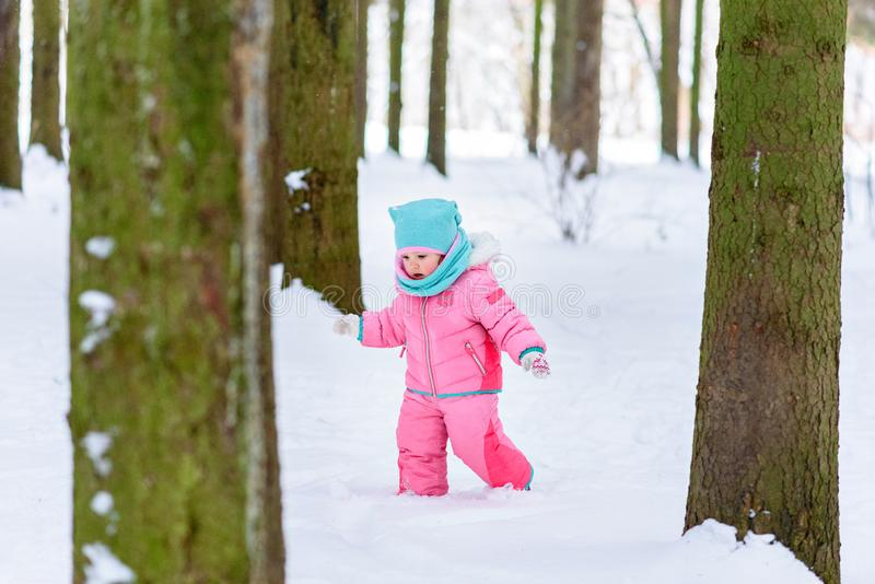 Little girl in a pink jumpsuit walks in a snowy winter park stock photo