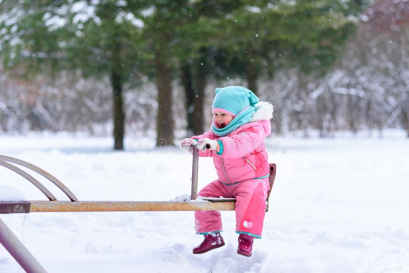 Little girl in a pink jumpsuit walks in a snowy winter park royalty free stock photography