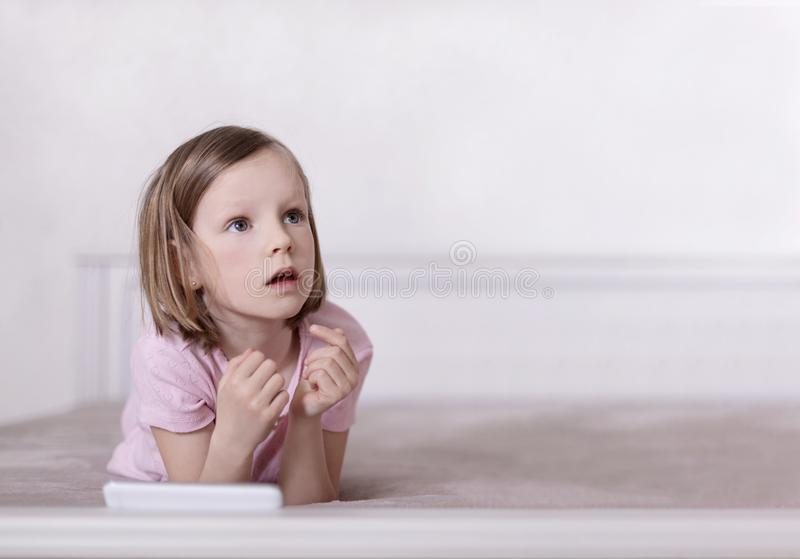 Little girl in pink pajamas on the bed is looking at a smartphone stock photos