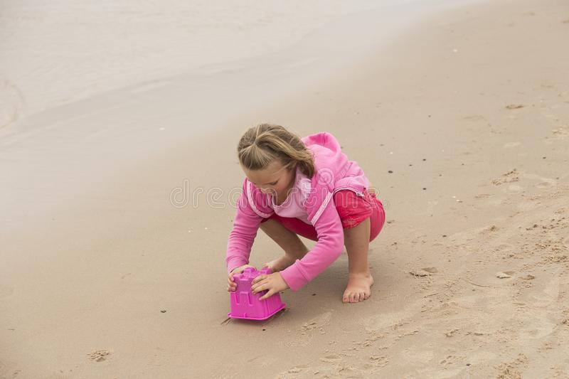 Little girl in pink playing with a pink bucket stock photos