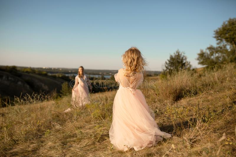 A little girl in a pink princess dress goes to meet her mom royalty free stock photography