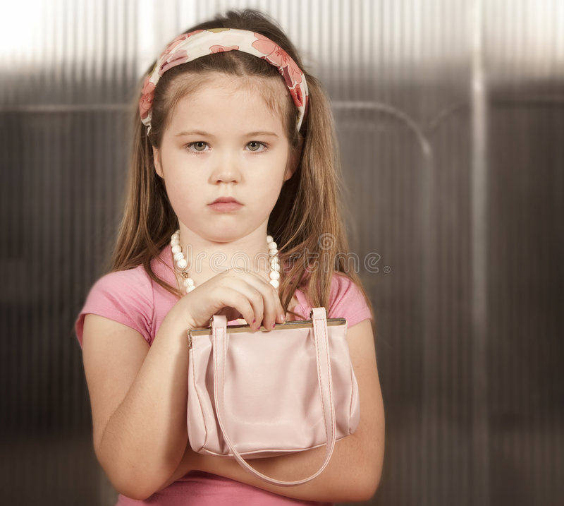 Little girl with pink purse royalty free stock image