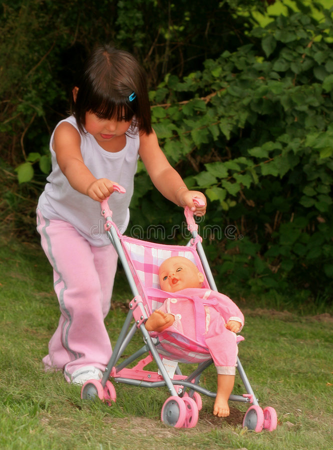Little Girl in Pink Pushing a Dolly in a Pram.