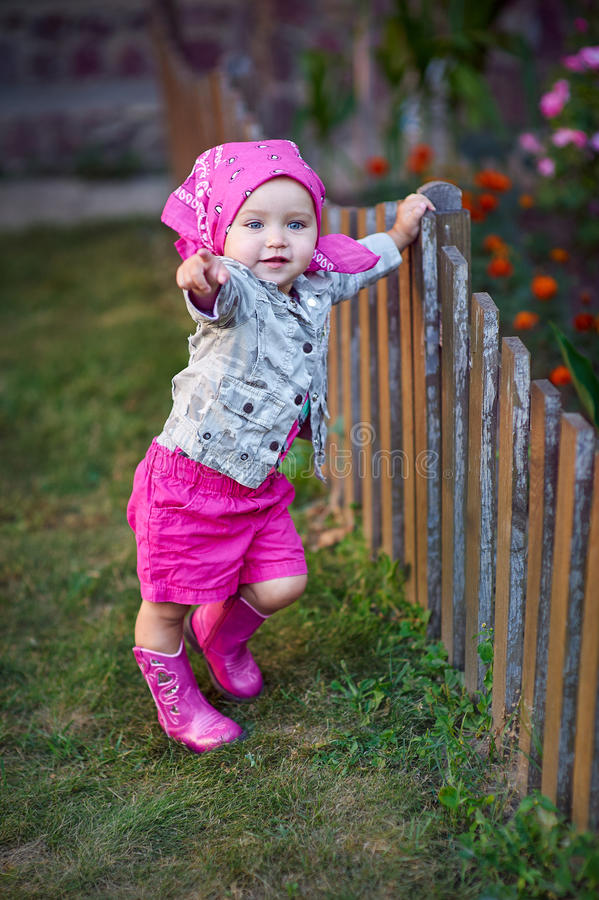 Little girl in pink shoes near the fence stock photos