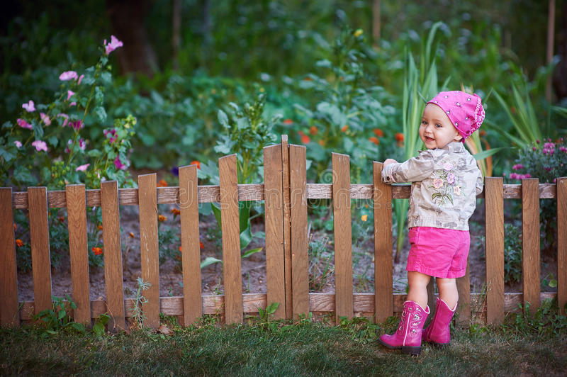 Little girl in pink shoes near the fence stock photography