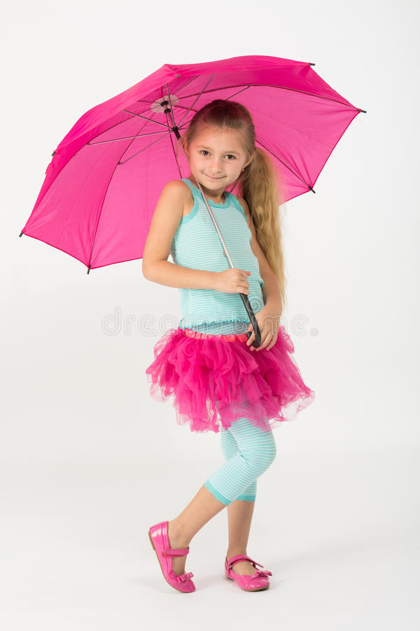 A little girl in pink skirt is chilly with umbrella. A little girl in a pink skirt is chilly with a pink umbrella stock image