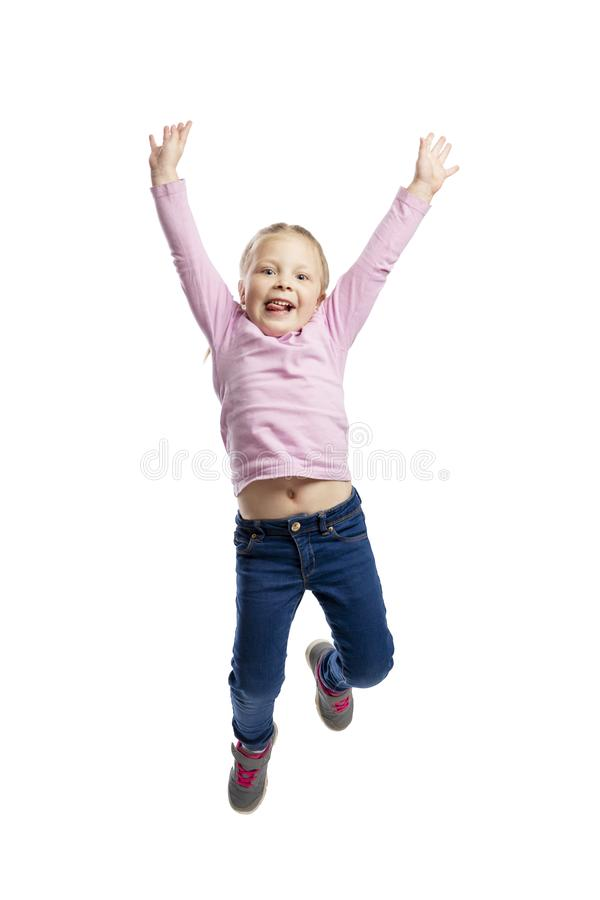 A little girl in a pink sweater and jeans joyfully jumps. Isolated over white background. royalty free stock photography