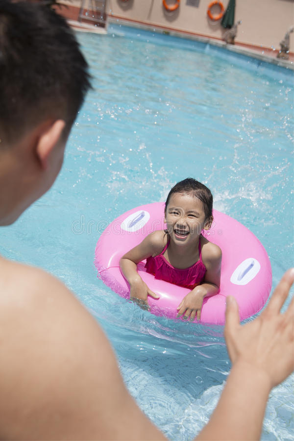 Little girl with a pink tube and her father swimming in the pool royalty free stock image