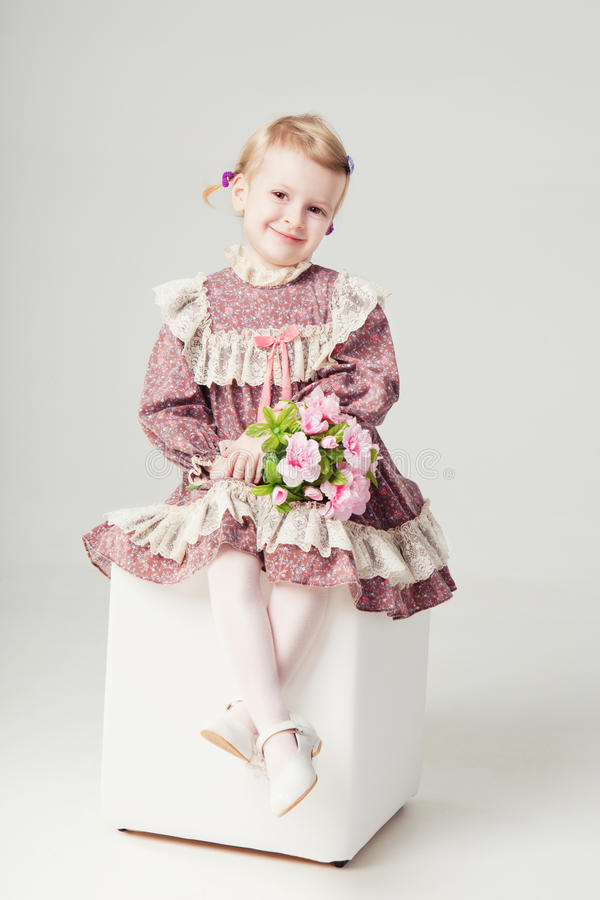 Little girl in pink-violet dress and bouquet flowers. Small girl is sitting on a white pouf and holding bouquet of roses. Studio shot. Gray background stock photo