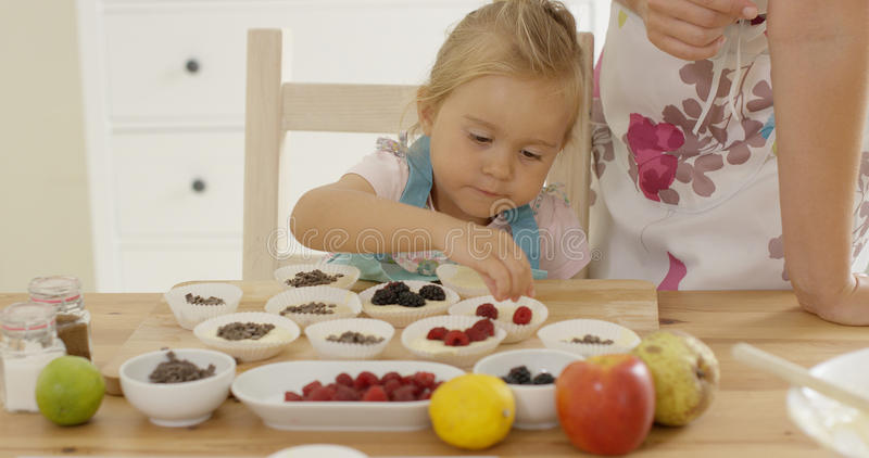 Little girl placing berries on muffins royalty free stock images