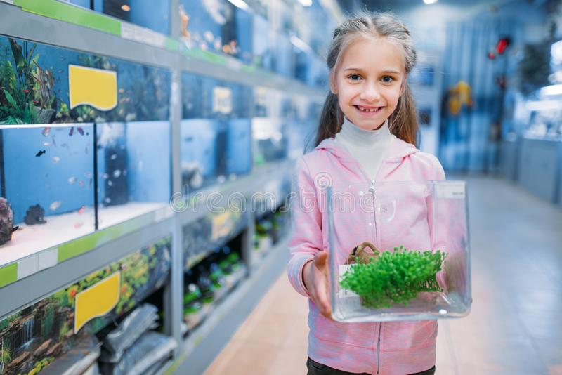 Little girl with plant for aquarium in pet shop stock images