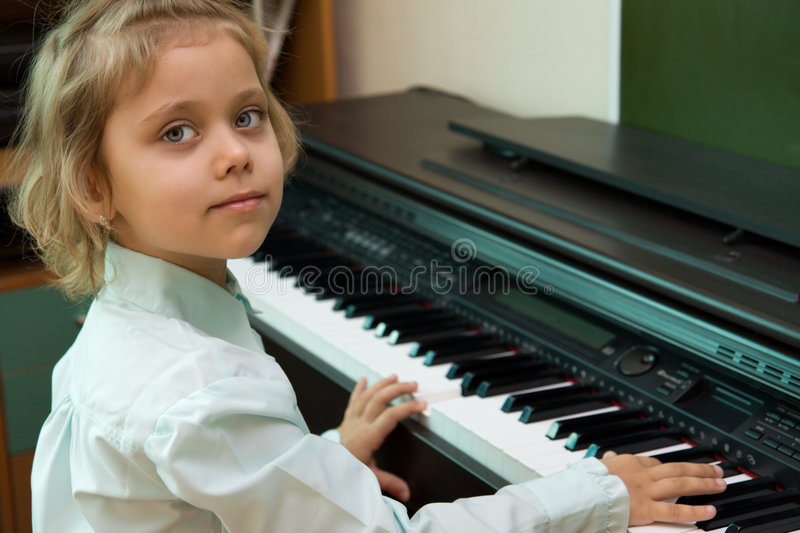 Little girl play on a electric piano royalty free stock photos