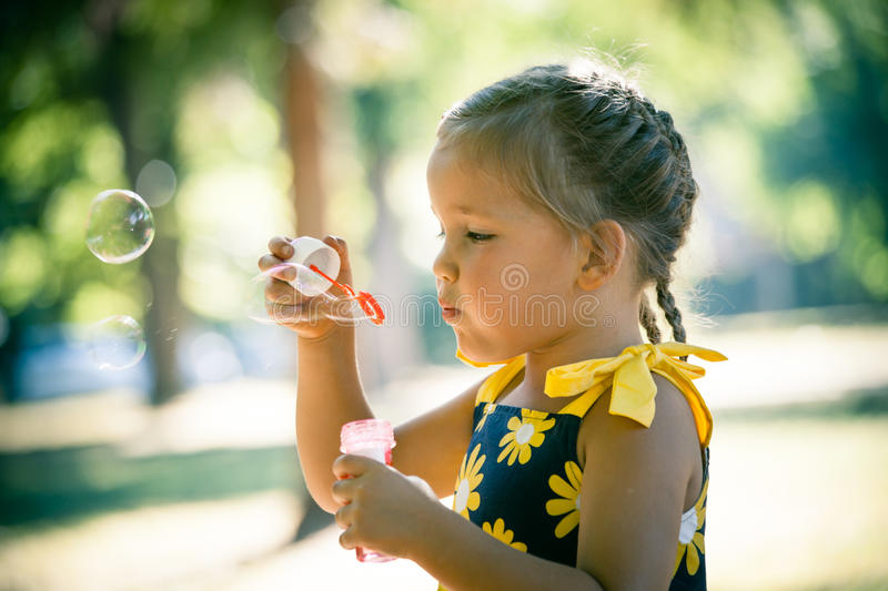 Little girl play in park blow soap bubbles profile close up stock photo