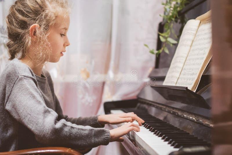 Little girl play the piano. stock photos