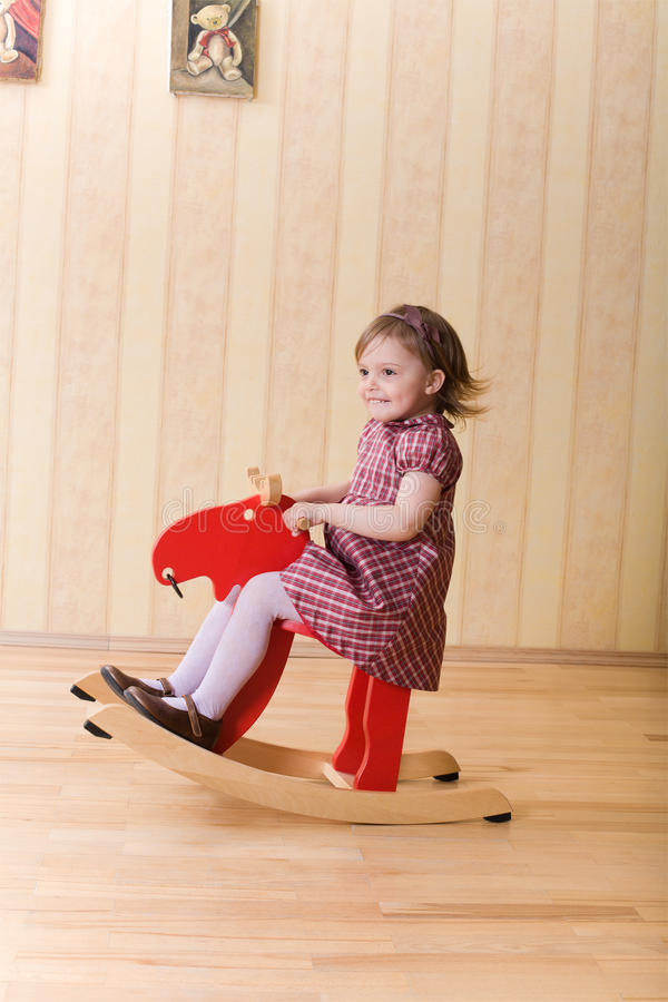 Little girl play with toy wooden deer. Happy little girl play with toy wooden deer royalty free stock photography