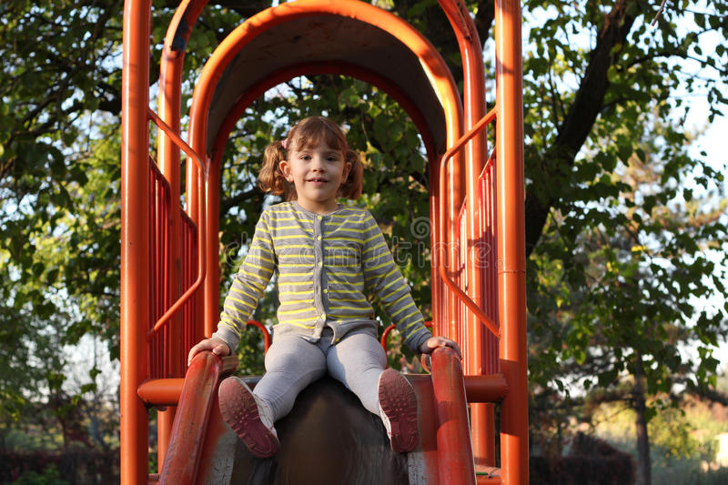 Download Little Girl On Playground Slide Stock Photo - Image: 27563176