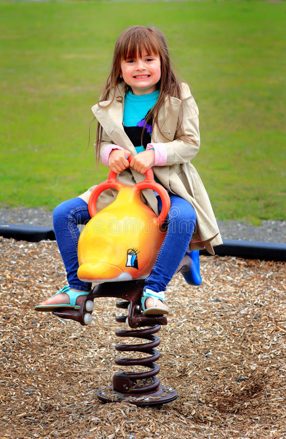 Little Girl on Playground Toy. A cute typical little preschool girl with long brown hair playing on a spring toy in a playground. Shallow depth of field stock images