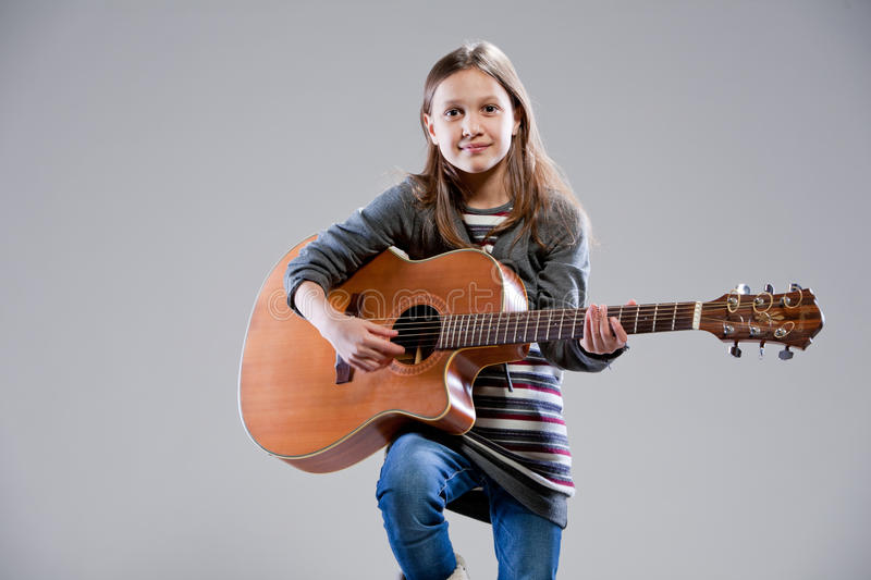 Little girl playing acoustic guitar. Baby playing an acoustic guitar royalty free stock image